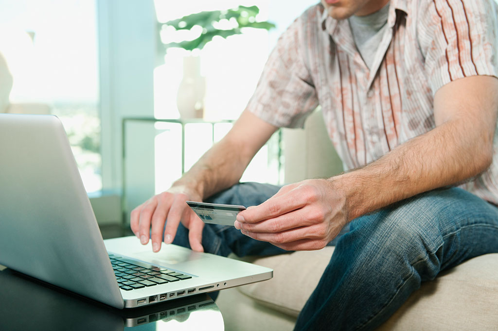 Caucasian man shopping online with credit card